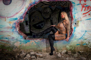 Tattooed blonde with large boobs models solo amid graffiti filled walls