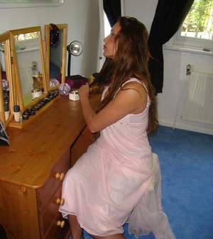 Older woman brushes her long hair in a mirror wearing nylons and garter belt