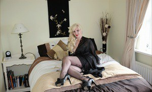 Curvy MILF with blonde hair goes topless in nylons and garters