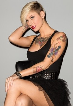 Tattooed female Kleio Valentien slips out of her black dress for nude poses