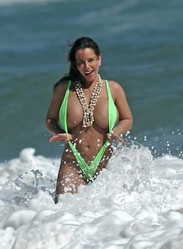 Amply endowed female Alicia Dimarco struts in a v-bikini amid foamy surf