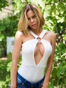 Solo girl Jennifer Ann sets her enhanced boobs loose in front of a greenery