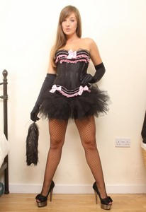 Solo girl Cate sports a tutu and black velvet gloves while toying on a bed