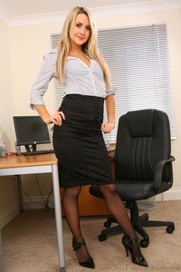 Horny office babe Charlie Rose bends over the desk and poses in lingerie