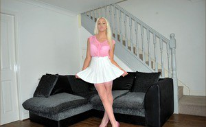 Hot blonde in pink sheer stockings drops her skirt to pose topless in thong