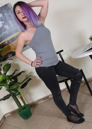 Clothed female with dyed hair removes flat shoes from hose covered feete