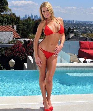 Blonde chick Randy Moore removes her bikini before toying her pussy by a pool