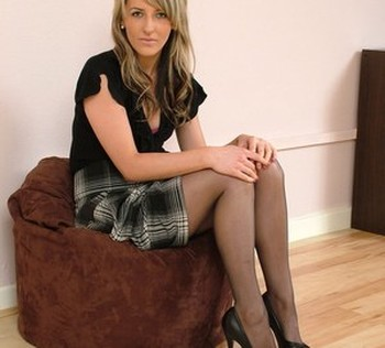 Dirty blonde model shows off her stiletto heels in a black hose and long skirt
