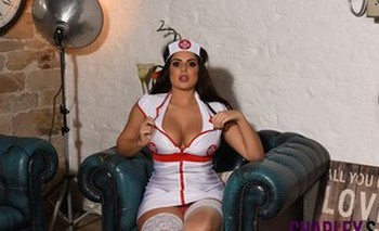 Sexy nurse Charlotte Springer displays her huge tits and strips her uniform