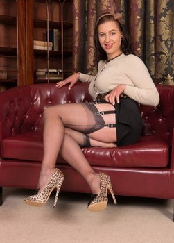 Classy lady Tindra Frost strips to nylons and vintage garters on loveseat