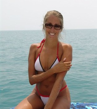 Middle-aged amateur with hairy arms models in a bikini next to the ocean