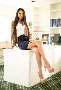 Leggy brunette removes miniskirt and lingerie to pose naked in high heels
