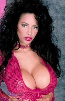 Dark haired woman Angelique lets out her massive melons and poses in stockings