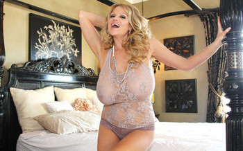 Blonde amateur Kelly Madison releases her huge breasts from see thru lingerie