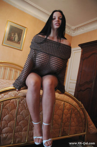 Black haired babe Joana exposes her huge boobs and flaunts them on a bed