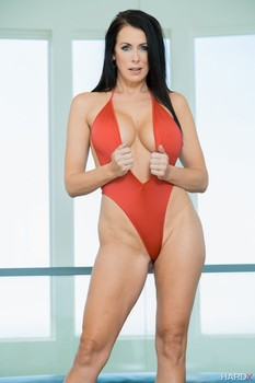 Stunning MILF in red Reagan Foxx flaunts fake tits and long legs