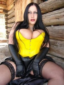 Goth model Lady Angelina exposes her huge tits and twat outside a log cabin