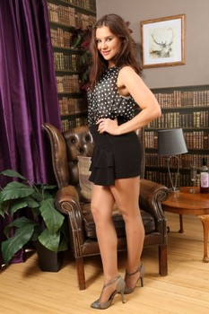 Dirty girl Saffron drops her black skirt and teases topless in pantyhose