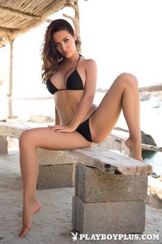 Erotic female centerfold Adrienn Levai in bikini spreading long legs outdoors