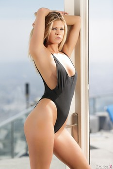 Hot blonde Scarlet Red peels off her one piece swimsuit in front of a window